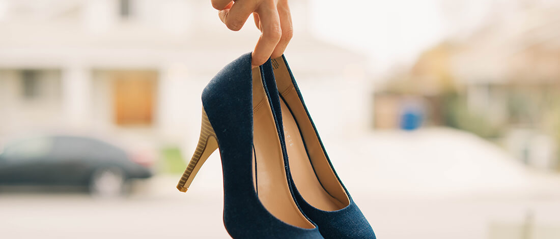 Hand holding pretty blue heels